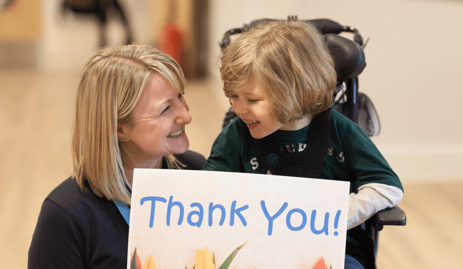 Little boy and nurses smiling and holding up 'Thank you' sign.