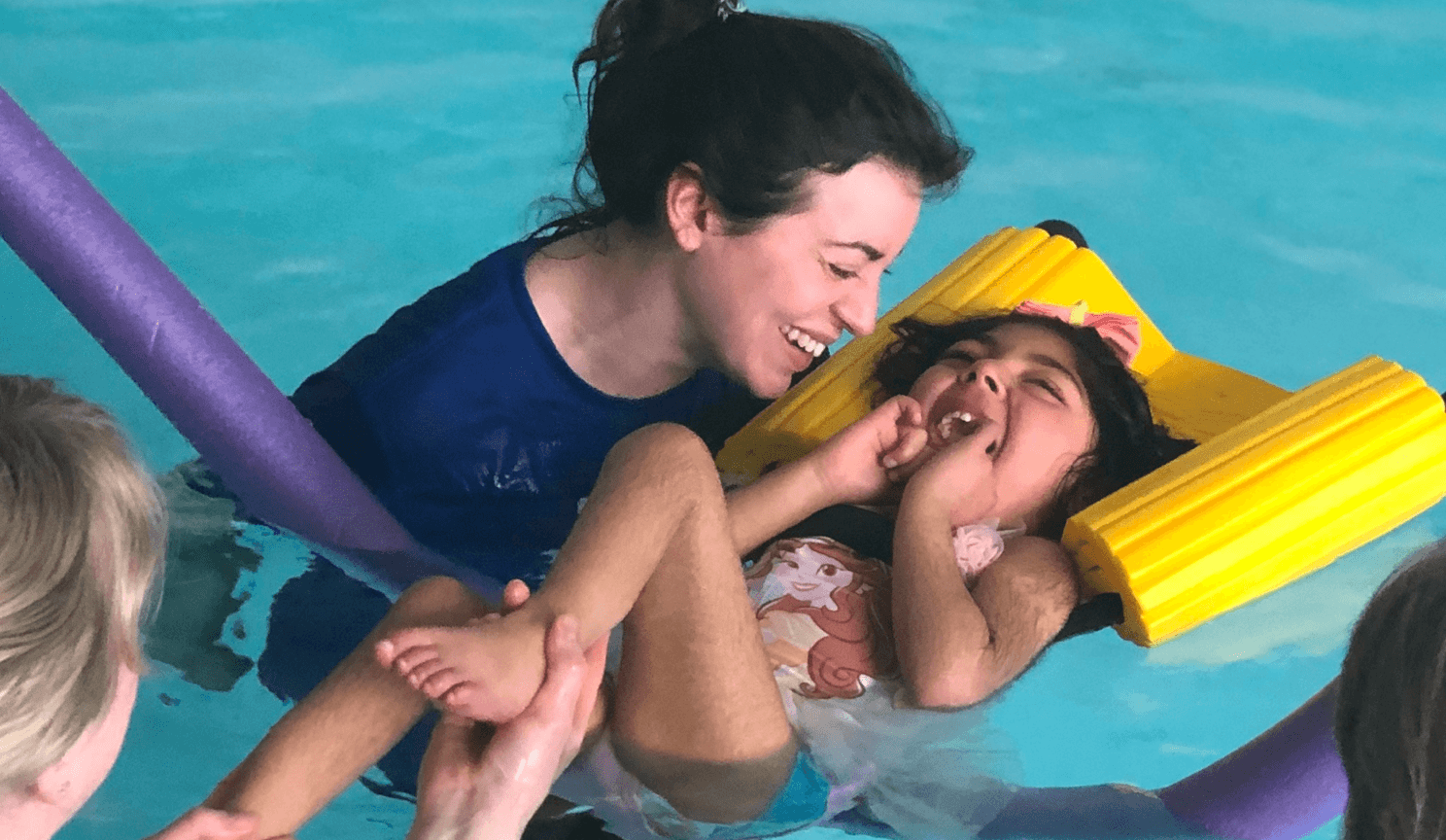Young girl and nurse playing in the hydrotherapy pool.