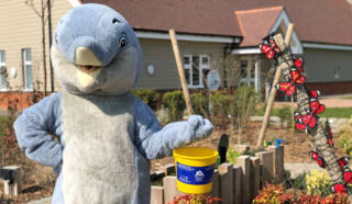 Alexander Devine Dolphin mascot with fundraising bucket.