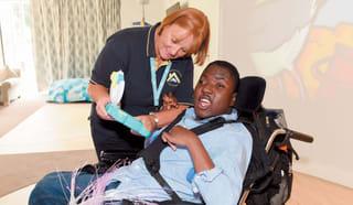 Boy in wheelchair laughing with Alexander Devine nurse.